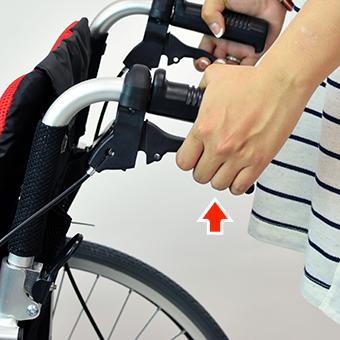 車椅子の介助ブレーキバーを握る