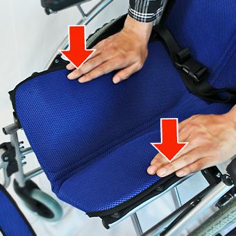車椅子座シートを上から下に押さえる